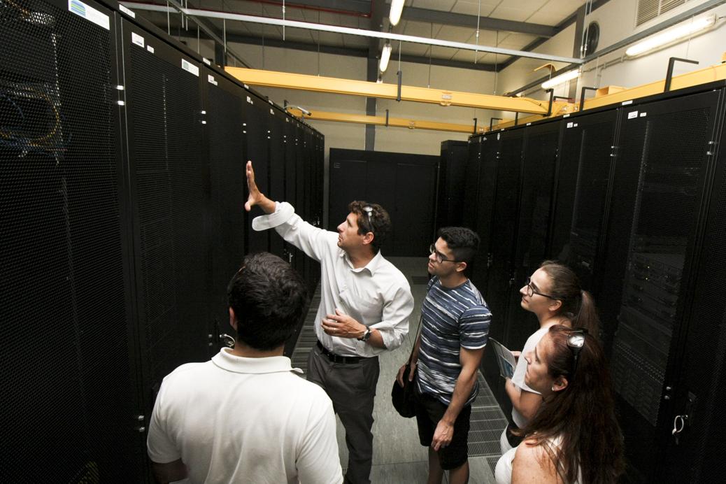 Um grupo de investigadores olham para um bastidor de servidores